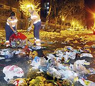 Barrenderos limpiando restos de un botellón. (Foto: EL MUNDO)