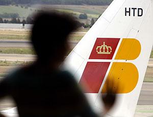 Un pasajero contempla el aterrizaje de un avión en Barajas. (Foto: REUTERS)