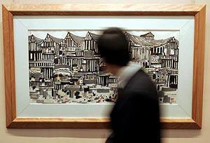 Un hombre pasa ante uno de los cuadros que serán subastados. (Foto: EFE)