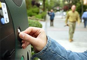 Un hombre echa dinero en un parquímetro de una céntrica calle de Madrid. (EM)