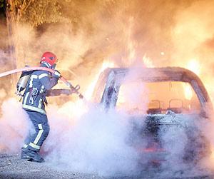 Un bombero apaga un coche en Les Mureaux, al noroeste de París. (Foto: AP)