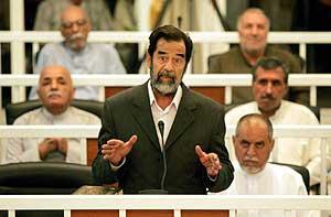 El abogado Adil al-Zubeidi a la derecha de Sadam en el juicio. (Foto: EFE).