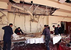 Trabajadores del Radisson limpian la sala donde se celebraba una boda. (Foto: REUTERS)