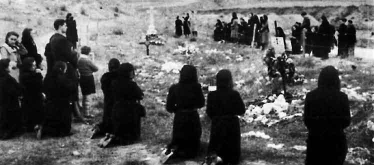 Familiares de algunas de las víctimas rezan ante las fosas comunes donde se enterró a los asesinados. (Foto: EL MUNDO)