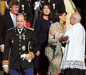 Alberto II y sus hermanas salen de la catedral de Mónaco tras la misa de entronización. (AFP)