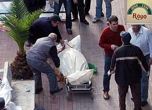 Operarios de una funeraria trasladan el cadáver de una de las víctimas del atraco. (Foto: EFE)