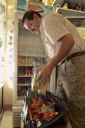 Un comerciante de Santa Cruz tira lo que tenía en el frigorífico. (Foto: EFE)