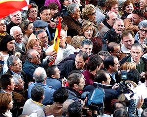 Los dos militantes del PP, cerca del ministro Bono, en la manifestación. (Foto: EFE)
