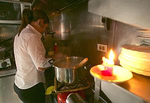 Una camarera de un bar de Santa Cruz de Tenerife prepara unos bocadillos a la luz de una vela. (Foto: EFE)