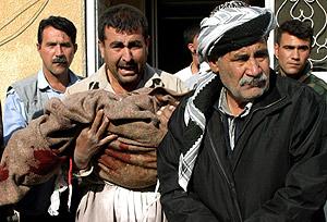 Un iraquí sostiene la manta ensangrentaba que cubría a un familia muerto. (Foto: AFP)