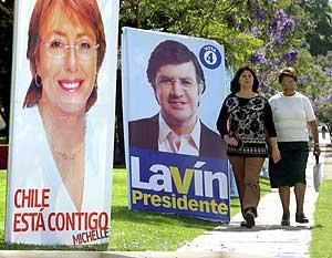 Dos mujeres pasean por Santiago de Chile, junto a dos carteles electorales. (Foto: AFP)