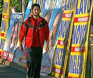 Un peatón pasa delante de varios carteles electorales en Colina. (AFP)
