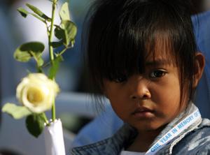 Una niña lleva una flor a las víctimas en Tailandia. (Foto: REUTERS)