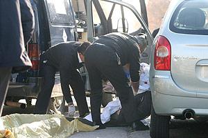 Dos agentes retiran el cuerpo del conductor tiroteado, Gaspar G. (Foto: Fernando Ruso)