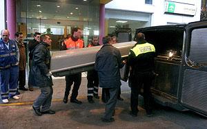 Los servicios funerarios introducen el féretro de uno de los fallecidos en un coche fúnebre. (EFE)