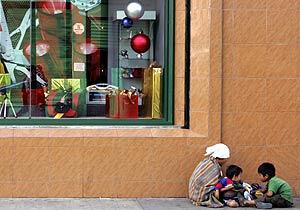 Una madre con sus hijos mendigando. (Foto: AFP)