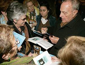 Fraga firma unas biografías al comienzo del congreso que celebra el PP de Galicia. (Foto: EFE)