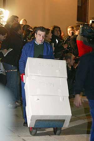 Un operario sale del Archivo con parte de los documentos. (Foto: EFE)