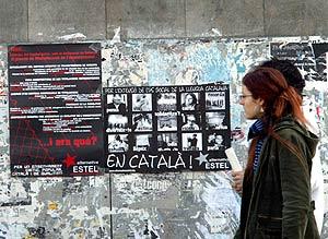 Dos jóvenes pasan por delante de un cartel en favor del uso del catalán en la Universidad de Bellaterra, en Barcelona. (Foto: A. Moreno)