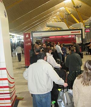Pasajeros indignados esperan en un mostrador de Iberia, atendido por un solo empleado. (R. Bécares)