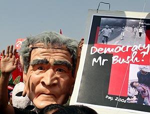 Un hombre muestra un cartel que compara las guerras de Vietnam e Irak. (Foto: REUTERS)