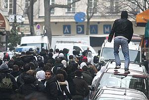 Un manifestante para por encima de un coche en París. (Foto: EFE)