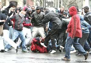 Jóvenes de los suburbios pegan a un estudiante en la manifestación de París. (Foto: REUTERS)