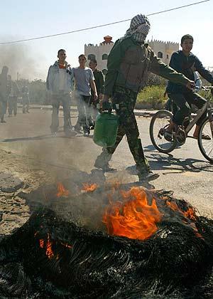 Un palestino pasa cerca del coche en llamas tras el atentado suicida. (Foto: REUTERS)