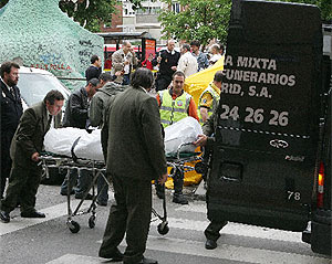 Operarios de la funeraria trasladan el cadáver de la mujer asesinada. (EFE)
