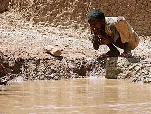 Un niño somalí bebe agua en una presa artificial en la localidad de Bur Dhuxunle. (Foto: REUTERS)