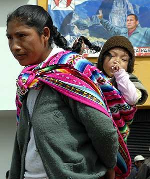 Una mujer indígena peruana camina con su hijo a la espalda. (Foto: EFE)
