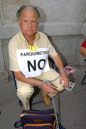 Un vecino, encadenado a un parquímetro de cartón la pasada semana. (Foto: EFE)