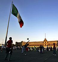 Unos niños juegan al fútbol bajo la bandera mexicana que preside el Zócalo. (Foto: AP)