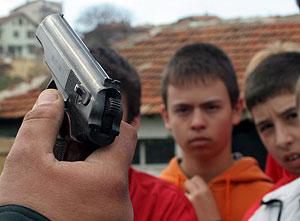 Unos chicos mirando a una pistola Makarov en Sofía, Bulgaria. (Foto: EFE)