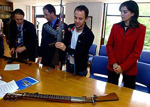 El colombiano César López recibe dos armas que serán convertidas en guitarras. (Foto: EFE)