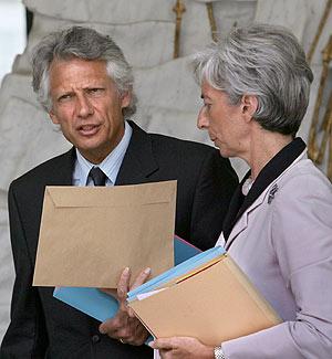 Villepin habla con una ministra tras la reunión semanal con Chirac. (Foto: AFP)