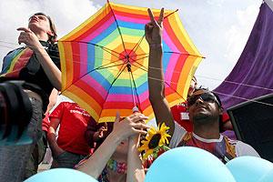 Varios manifestantes bajo un paraguas con el estandarte arcoiris. (Foto: EFE)