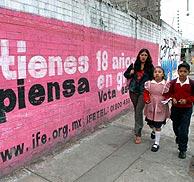 Una mujer y sus hijos pasan ante un cartel electoral. (Foto: EFE)