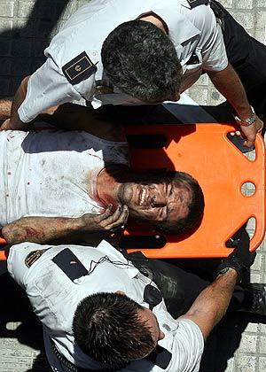 Dos policías trasladan a uno de los heridos en el siniestro. (Foto: AP)