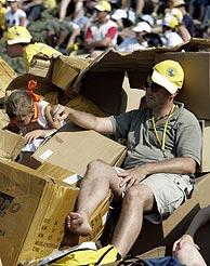 Un peregrino entre cajas de cartón. (Foto: EFE)