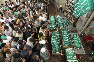 Palestinos rezan junto a varios de los cadáveres de una misma familia muertos por un ataque israelí. (Foto: AFP)