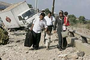 Una familia libanesa cruza un puente atacado por Israel. (Foto: EFE)