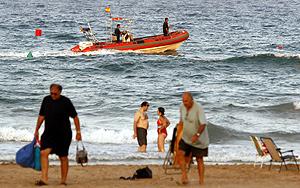Una lancha de la Policía Local patrulla por la zona de baño de San Juan. (Foto: EFE)