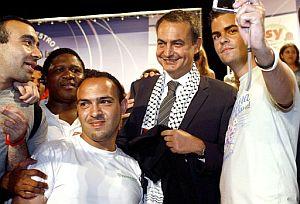 El presidente del Gobierno, fotografiado con unos jóvenes saharauis que le colocaron el pañuelo en la Universidad de Alicante. (Foto: Efe)