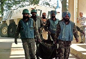 Funcionarios de la ONU llevan el cuerpo de uno de los fallecidos. (Foto: AP)