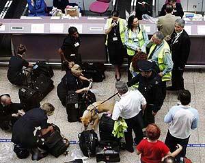 Pasajeros sacando sus enseres personales del equipaje de mano en Glasgow. (Foto: AP)