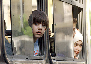 Niños libaneses abandonan en autobús los suburbios de Beirut . (Foto: EFE)