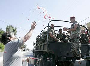 Una mujer lanza arroz y flores al paso de los soldados libaneses. (Foto: EFE)