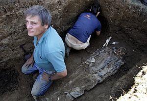 Dos voluntarios durante las labores de exhumación. (Foto: AFP)