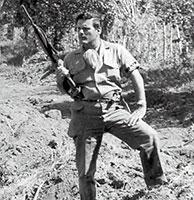 Frank Sturgiss el 11 de enero de 1959 en la loma de San Juan, al este de Santiago de Cuba. Posa con gesto aguerrido y empuñando su carabina M-2 sobre la tumba de los cerca de 200 batistianos fusilados un par de noches atrás.